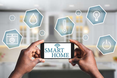 Photo for Man using phone application for controlling smart home indoors, closeup - Royalty Free Image
