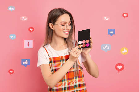 Photo pour Beauty blogger with brush and eyeshadow palette on pink background - image libre de droit
