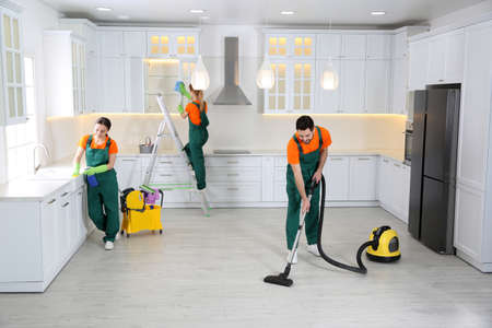Photo for Team of professional janitors cleaning modern kitchen - Royalty Free Image