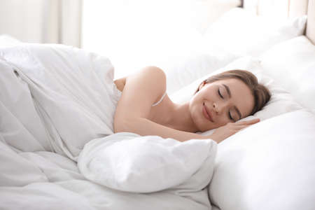 Photo pour Young woman sleeping on comfortable pillow in bed at home - image libre de droit
