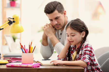 Photo for Man helping his daughter with homework at table indoors - Royalty Free Image