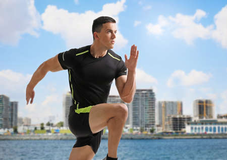 Photo pour Athletic young man running near sea on sunny day - image libre de droit