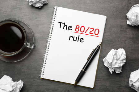 Pareto principle concept. Notebook with 80/20 rule representation on grey background, flat lay