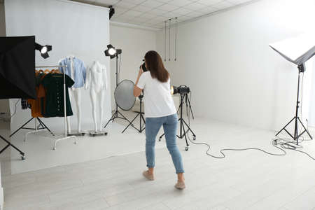 Photo pour Professional photographer taking picture of ghost mannequins with modern clothes in photo studio - image libre de droit