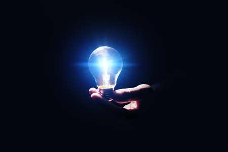Photo pour Idea concept. Man with glowing light bulb in darkness, closeup - image libre de droit