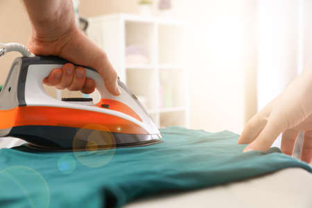 Photo for Man ironing clothes on board at home, closeup - Royalty Free Image