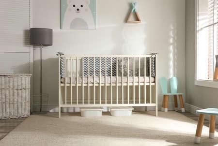 Photo pour Cute baby room interior with crib and decor elements - image libre de droit