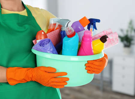 Photo for Woman holding basin with cleaning supplies in office, closeup - Royalty Free Image