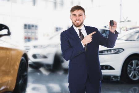 Photo pour Happy salesman with key in car salon - image libre de droit