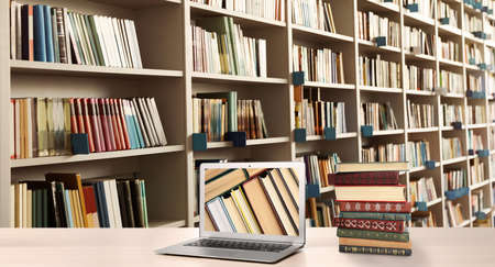 Photo for Digital library concept. Modern laptop on table and shelves with books indoors - Royalty Free Image