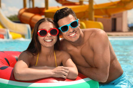 Photo for Happy couple with inflatable ring at water park. Summer vacation - Royalty Free Image