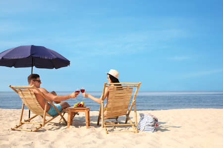 Photo for Happy couple with wine on sunny beach at resort - Royalty Free Image