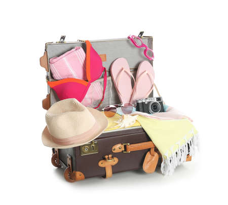 Photo pour Open vintage suitcase with different beach objects packed for summer vacation isolated on white - image libre de droit
