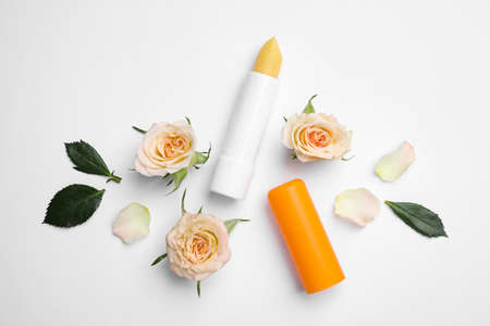 Photo pour Hygienic lipstick and rose flowers on white background, top view - image libre de droit