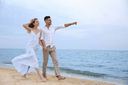 Photo for Happy couple having romantic walk on beach. Space for text - Royalty Free Image