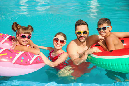 Photo for Happy family with inflatable rings in swimming pool - Royalty Free Image
