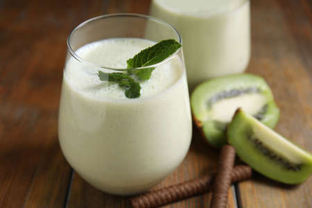Photo for Tasty milk shake with kiwi on wooden table, closeup - Royalty Free Image