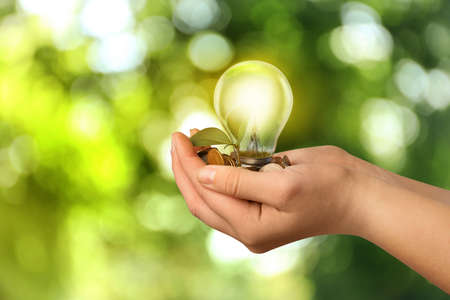 Photo pour Solar energy concept. Woman holding glowing light bulb with seedling and coins against green blurred background, closeup - image libre de droit