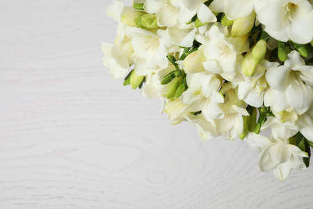 Photo for Beautiful freesia flowers on white wooden background, above view. Space for text - Royalty Free Image