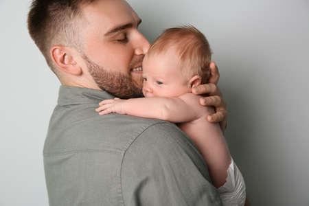 Photo pour Father with his newborn son on light gray background - image libre de droit