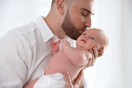 Photo pour Father with his newborn son on light background, closeup - image libre de droit