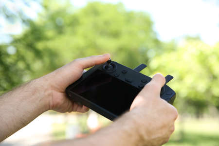 Man holding new modern drone controller outdoors, closeup of hands