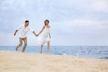 Photo for Happy couple running on beach, space for text. Romantic walk - Royalty Free Image