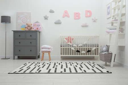 Foto de Cute baby room interior with crib and chest of drawers near white wall - Imagen libre de derechos