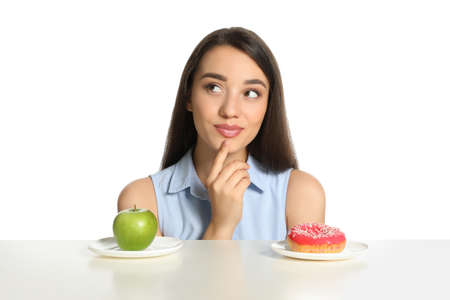 Photo for Doubtful woman choosing between apple and donut at table on white background - Royalty Free Image