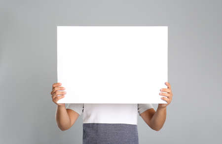 Photo for Man holding white blank poster on gray background. Mockup for design - Royalty Free Image