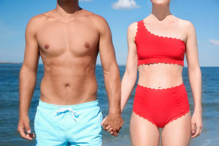 Photo for Woman in bikini and her boyfriend on beach, closeup. Lovely couple - Royalty Free Image