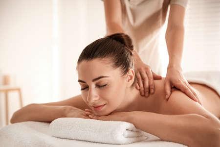 Foto de Young woman receiving shoulder massage in spa salon - Imagen libre de derechos