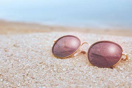 Photo for Stylish sunglasses on sandy beach near sea - Royalty Free Image