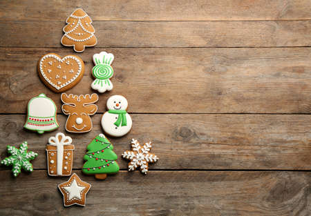 Photo for Christmas tree shape made of delicious gingerbread cookies on wooden table, flat lay. Space for text - Royalty Free Image