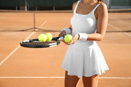 Photo for Sportswoman with racket and tennis balls at court, closeup - Royalty Free Image