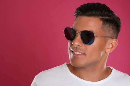 Photo for Handsome man wearing sunglasses on pink background, closeup. Space for text - Royalty Free Image