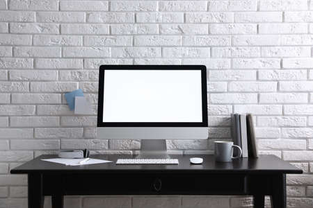 Photo for Comfortable workplace with modern computer on black table near white brick wall. Space for text - Royalty Free Image