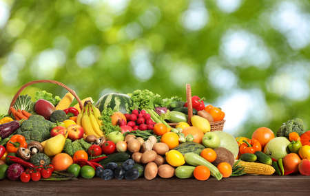 Photo for Assortment of fresh organic vegetables and fruits on wooden table against blurred green background - Royalty Free Image