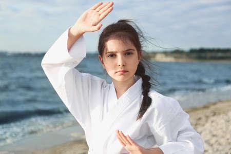 Photo pour Cute little girl in kimono practicing karate near river - image libre de droit