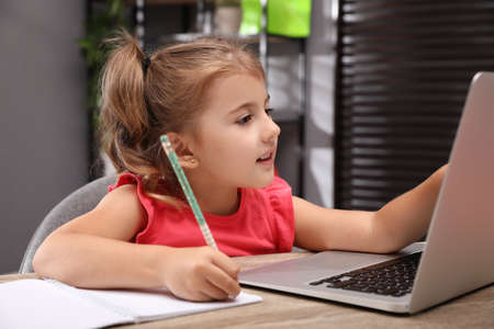 Photo for Cute little girl doing homework with laptop at table - Royalty Free Image