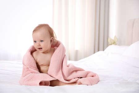 Photo pour Cute little baby with soft pink towel on bed after bath. Space for text - image libre de droit