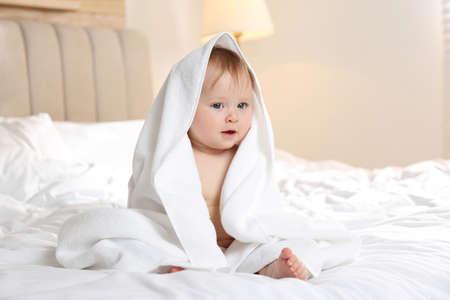 Photo pour Cute little baby with soft towel on bed after bath - image libre de droit