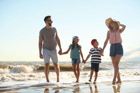 Photo for Happy family walking on sandy beach near sea - Royalty Free Image