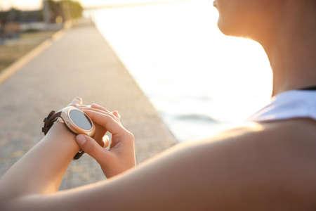 Photo pour Woman checking fitness tracker after training outdoors, closeup - image libre de droit