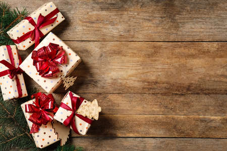 Photo for Christmas gift boxes with red bows on wooden background, flat lay. Space for text - Royalty Free Image