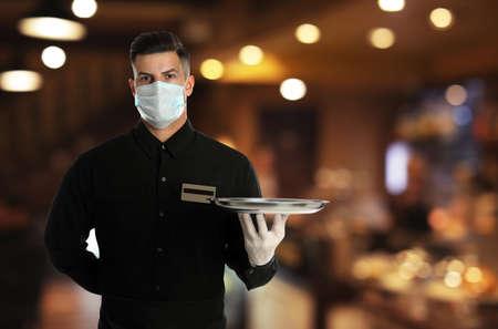 Foto de Waiter in medical face mask holding tray in restaurant - Imagen libre de derechos