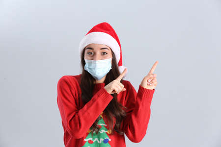 Photo for Beautiful woman wearing Santa Claus hat and medical mask on light gray background - Royalty Free Image