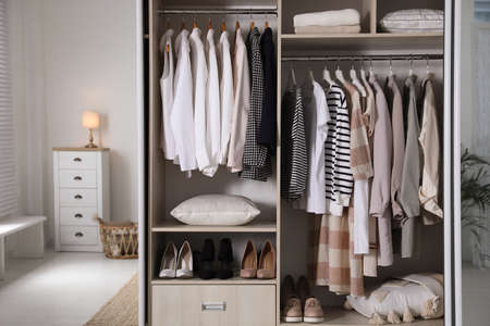 Photo pour Wardrobe closet with different stylish clothes, shoes and home stuff in room - image libre de droit