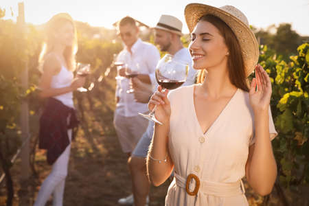 Photo for Beautiful young woman with glass of wine and her friends in vineyard on sunny day - Royalty Free Image