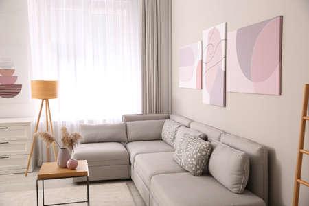 Foto de Stylish living room interior with big comfortable sofa and pictures - Imagen libre de derechos